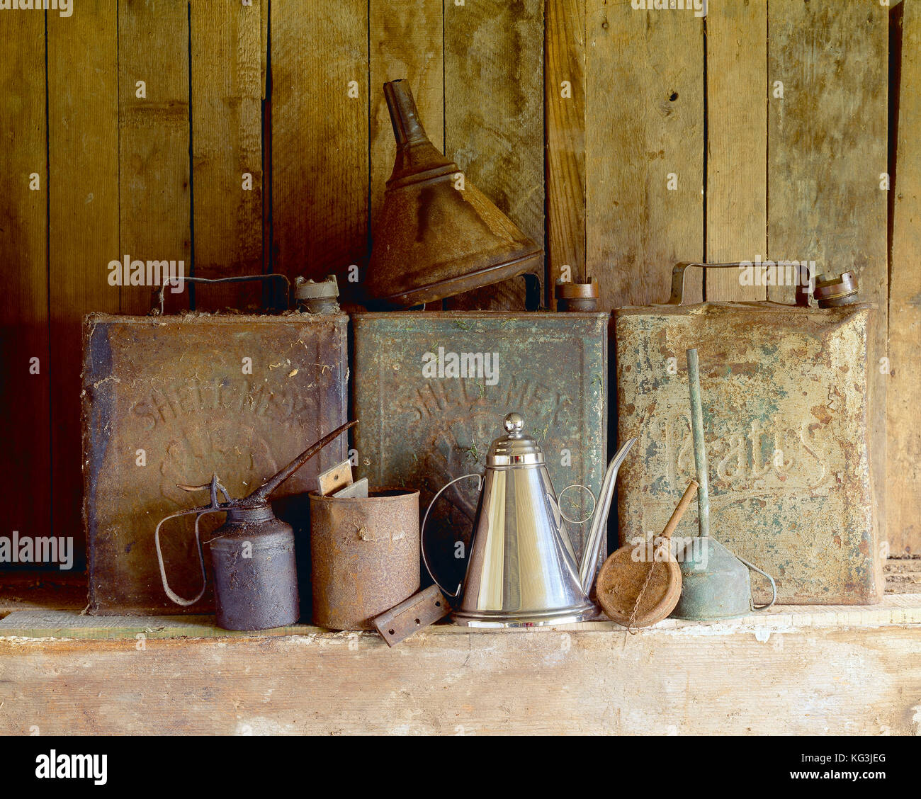 Still life. Antique petrol and oil cans on garage shelf. - Stock Image