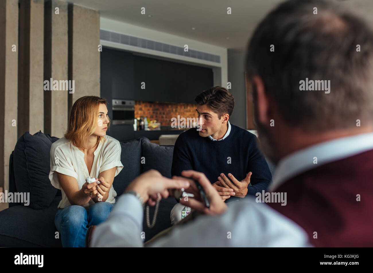 Man and woman sitting on couch and talking during psychotherapy session. Couple at psychotherapist to resolve their - Stock Image