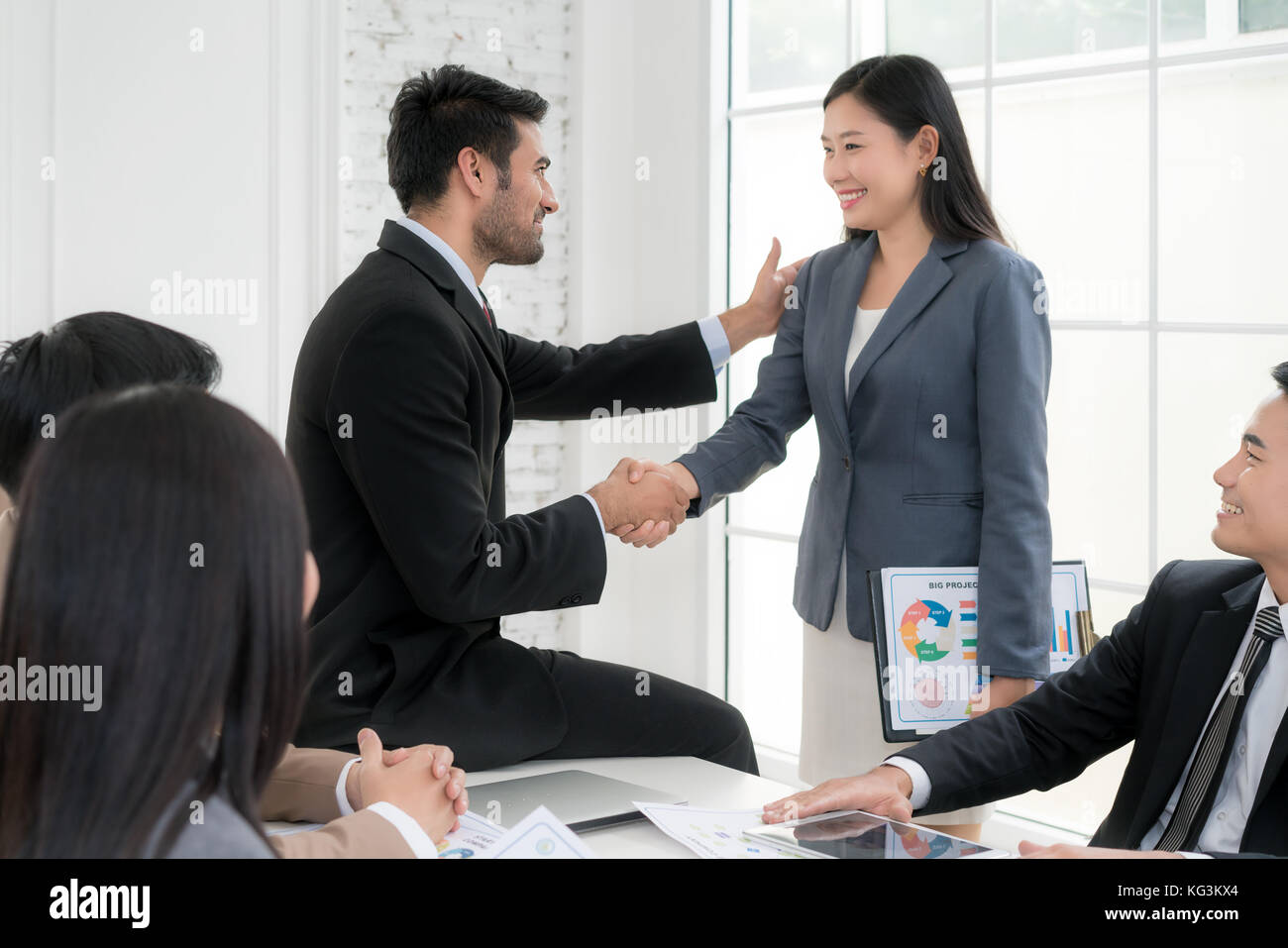 Asian businessman and businesswoman shaking hands in conference room. Business people shaking hands agreement concept. - Stock Image