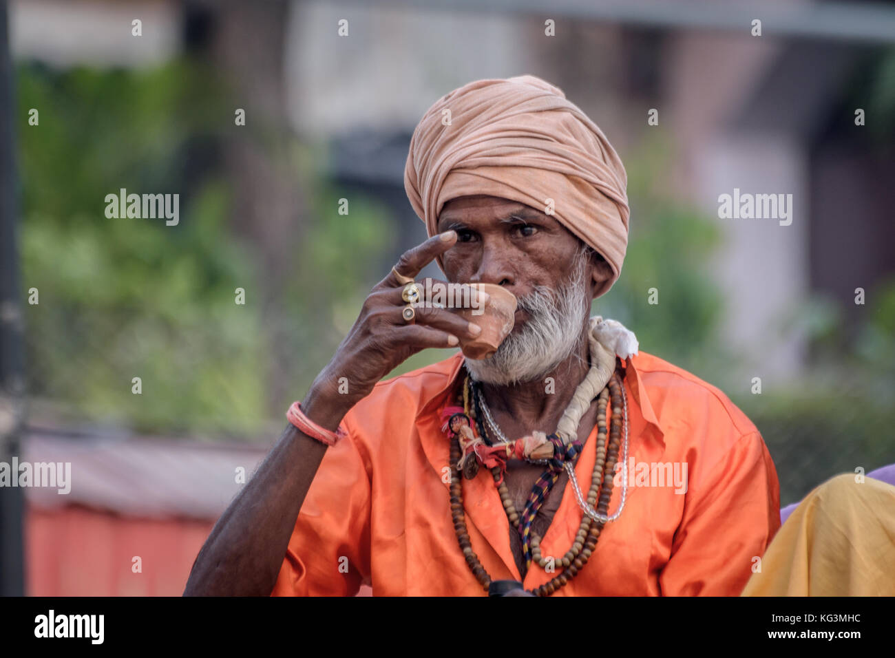 A sadhu baba is drinking tea on a clay pot at Varanasi ghat early in the morning. - Stock Image