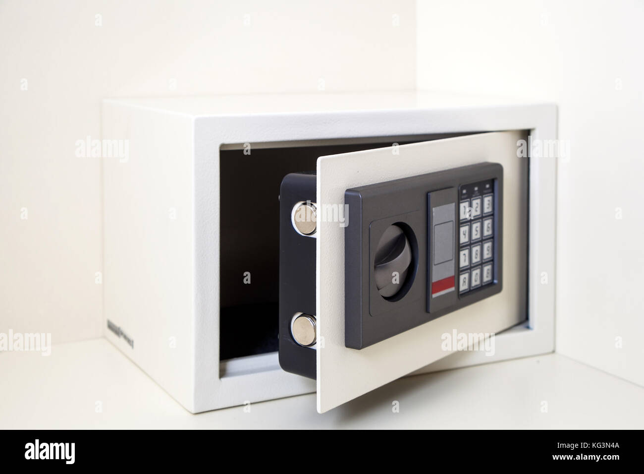 A close-up of a small metalic white safe with a combination lock for storing valuables with an open door cabinet - Stock Image