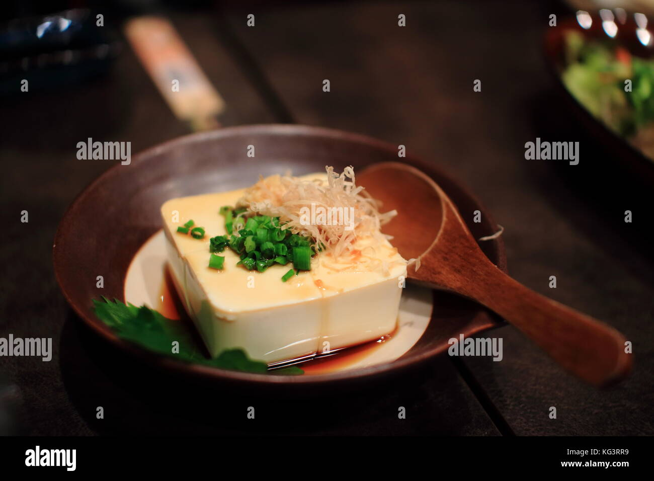 Japan tofu diced dish on wood table in a traditional Japanese restaurant. Healthy food. - Stock Image
