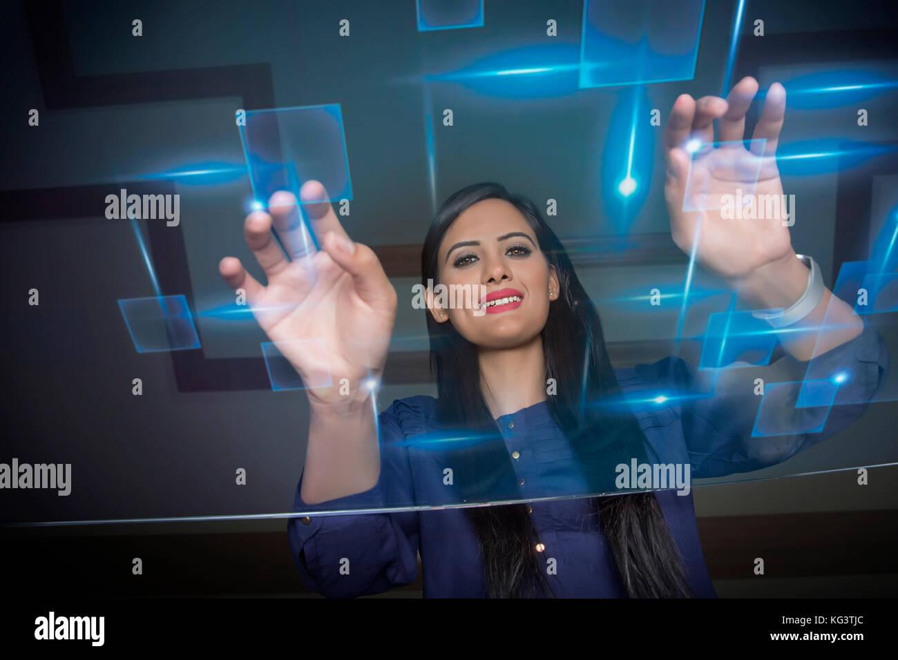 Businesswoman using futuristic computer keyboard - Stock Image