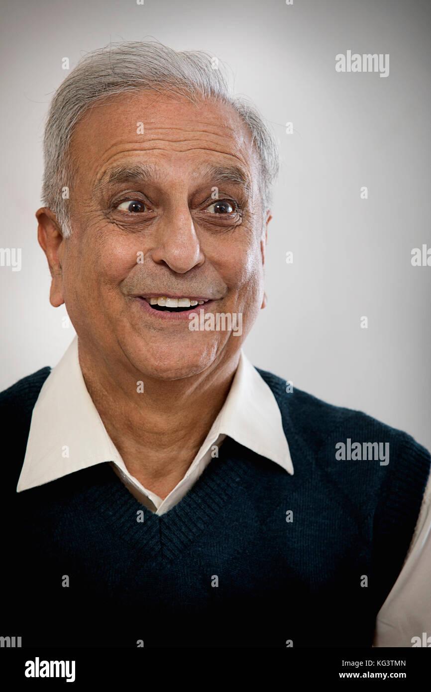Portrait of older happy man looking away - Stock Image