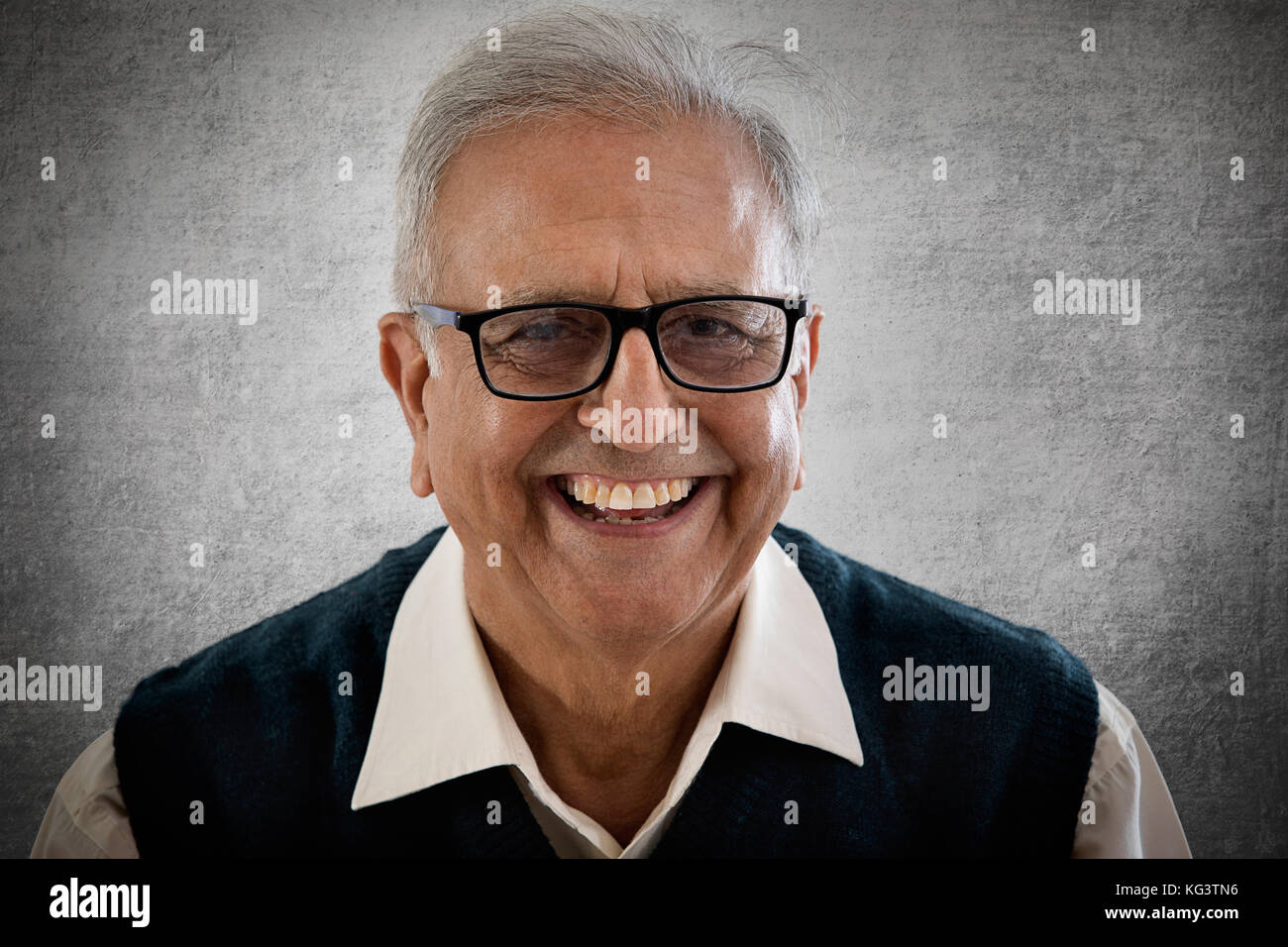 Portrait of smiling elderly man wearing spectacles - Stock Image