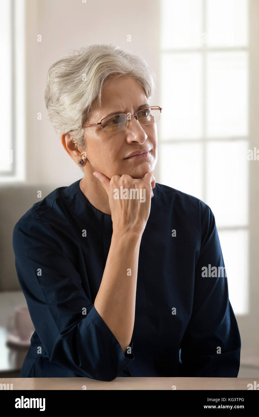 Mature woman thinking with hand on chin - Stock Image