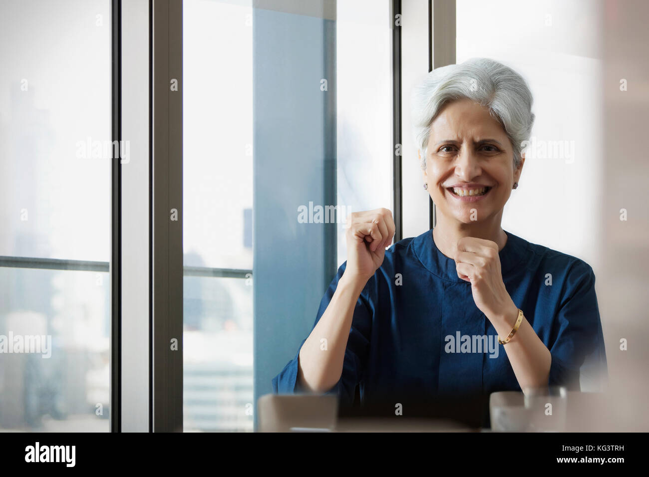 Smiling woman cheering with hand fists - Stock Image