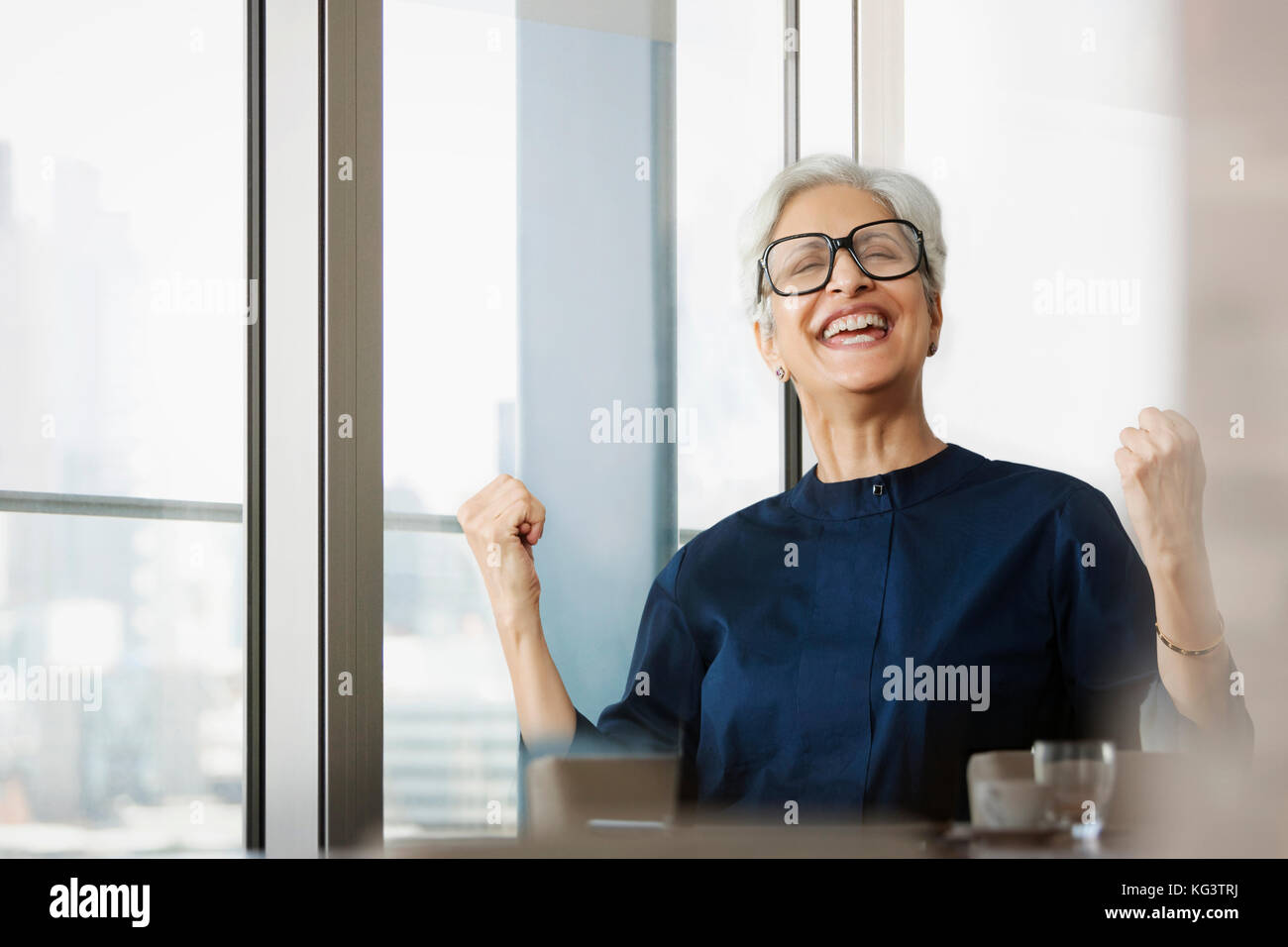 Smiling senior woman wearing eye glasses cheering with hand fists - Stock Image