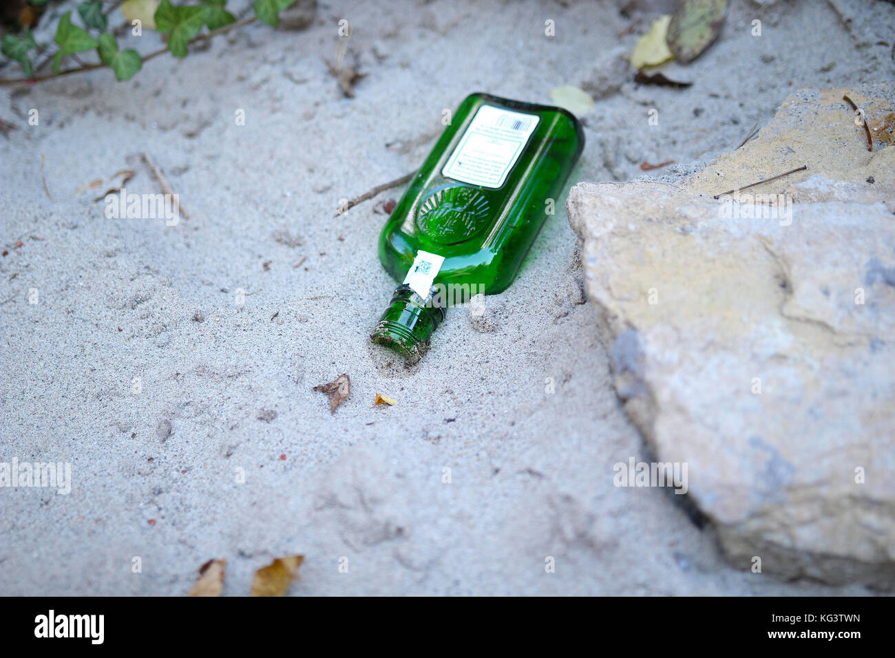 Dirty beach. Alcohol bottle on the beach sand. Sea pollution. - Stock Image
