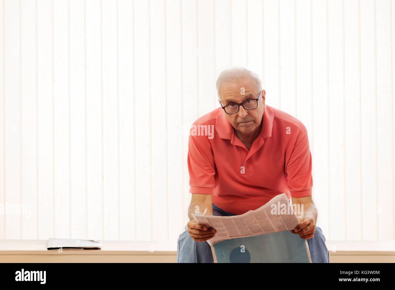 Senior Man reading newspaper sitting on bench at home - Stock Image