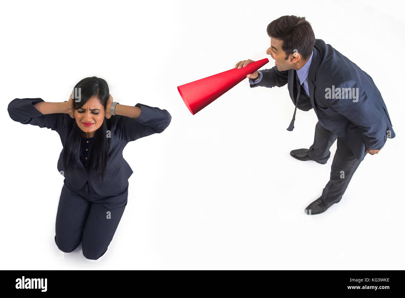 Businessman shouting through megaphone on businesswoman - Stock Image