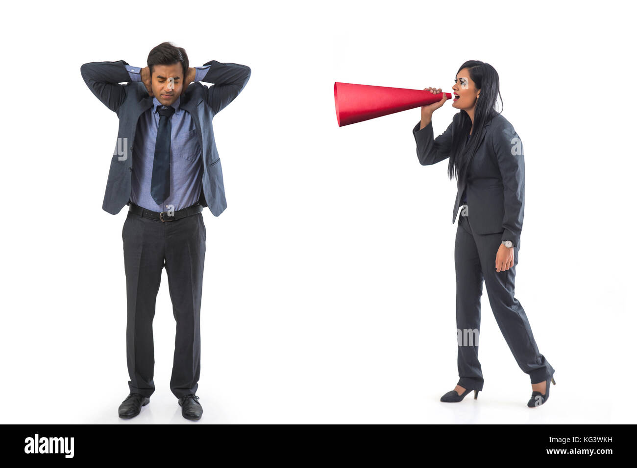 Businesswoman shouting through megaphone on businessman - Stock Image