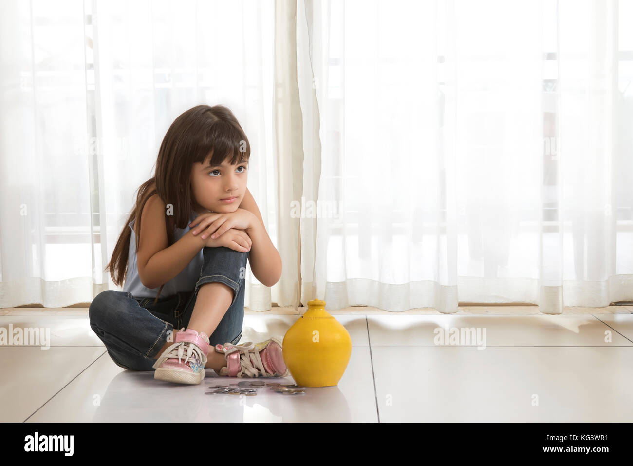 Little girl sitting on floor with clay piggy bank and coins - Stock Image