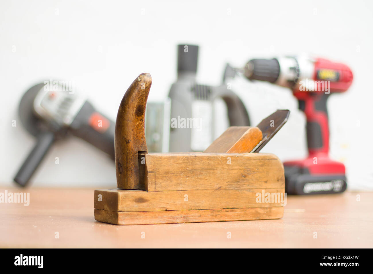 Old carpentry tools in the foreground. New power tools in the background. Old carpenter joinery in the foreground. - Stock Image