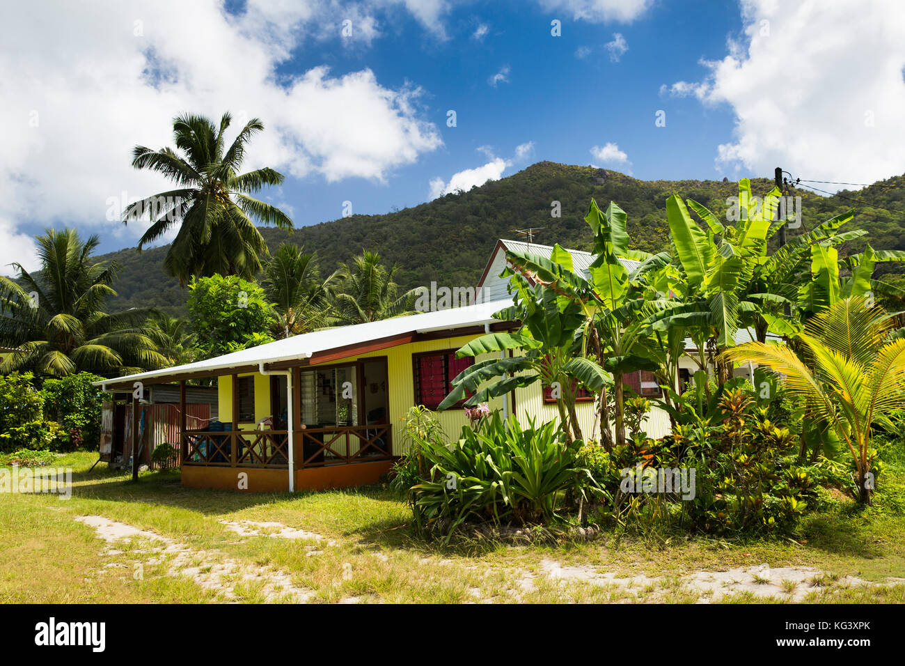 The Seychelles, Praslin, Grand Anse, traditional village house in lush tropical garden - Stock Image