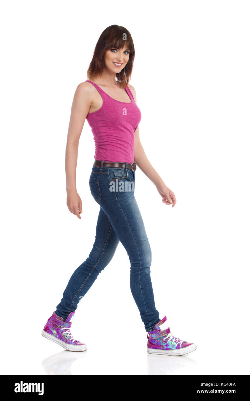 Young woman in jeans, magenta tank top and sneakers is walking and looking at camera. Side view. Full length studio - Stock Image