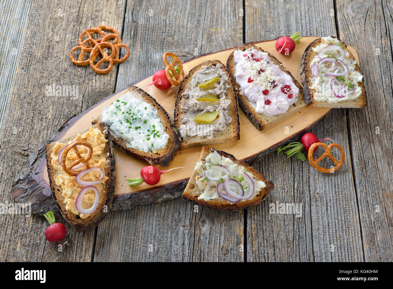 Hearty snack with different kinds of spreads on farmhouse bread served on an old wooden table - Stock Image