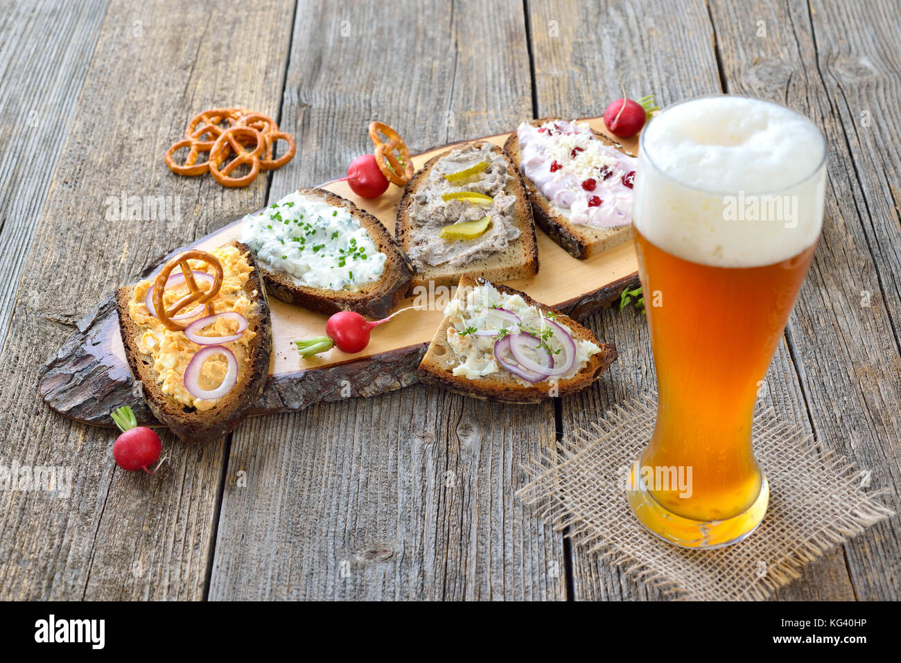 Hearty snack with different kinds of spreads on farmhouse bread served with a fresh yeast wheat beer on an old wooden - Stock Image
