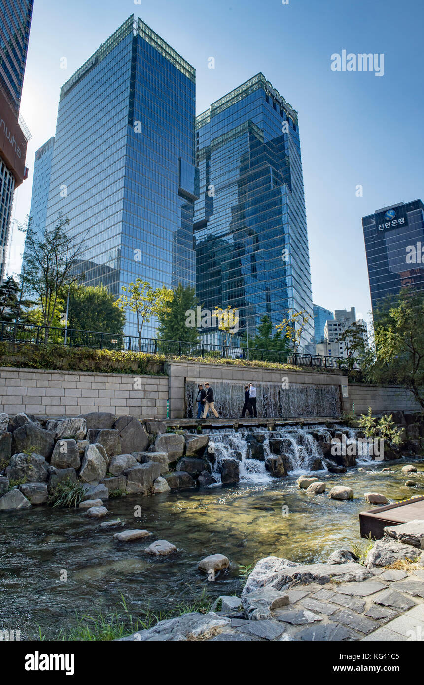 Skyscrapers and waterfall which refreshes and recycles the water from the Cheonggyecheon Stream, central Seoul in - Stock Image