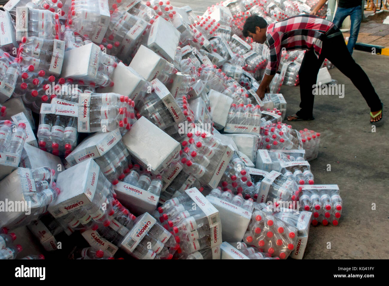 Men are moving cases of plastic purified water bottles on a city street in Phnom Penh, Cambodia. - Stock Image