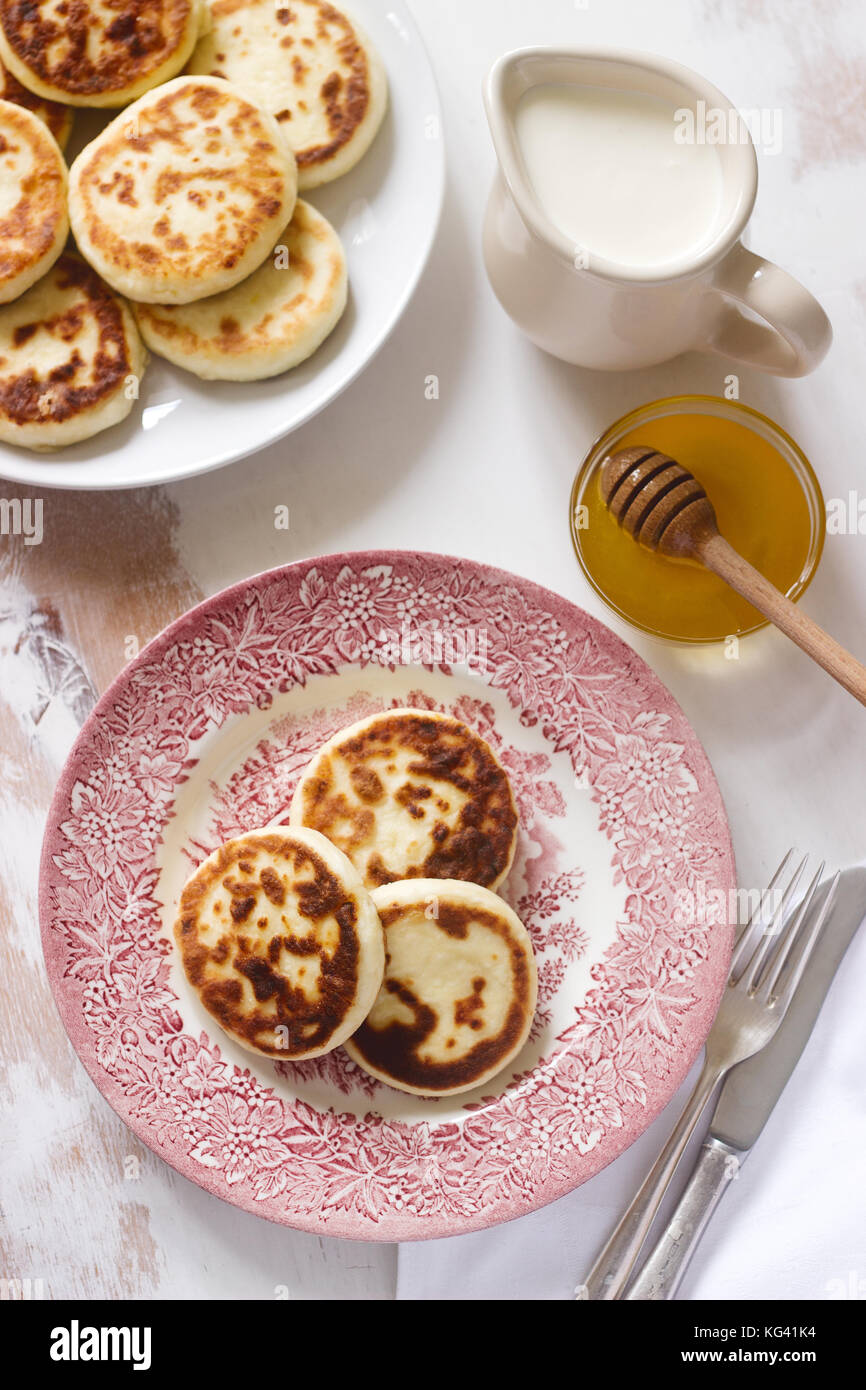Cottage cheese pancakes, homemade syrniki with honey and sour cream. - Stock Image