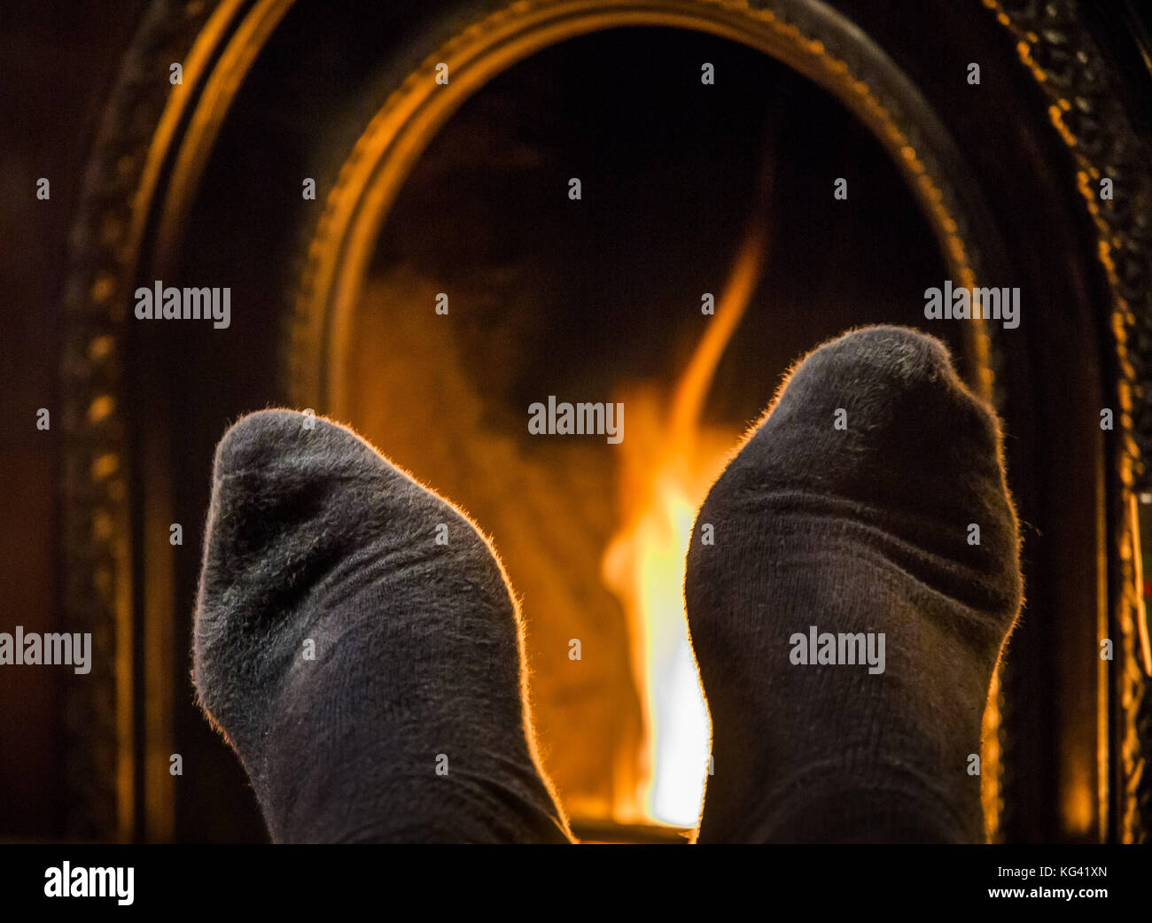 Warming feet by a cosy fireside. - Stock Image
