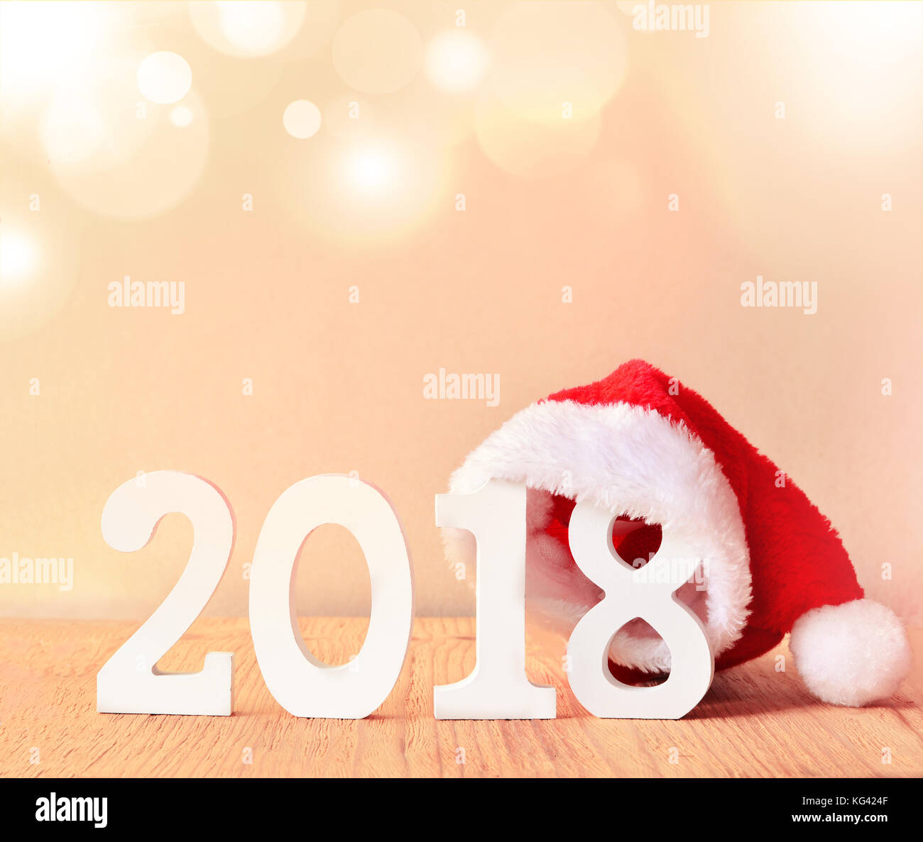 santa fur cap on a rustic wooden background with figures 2018 - Stock Image