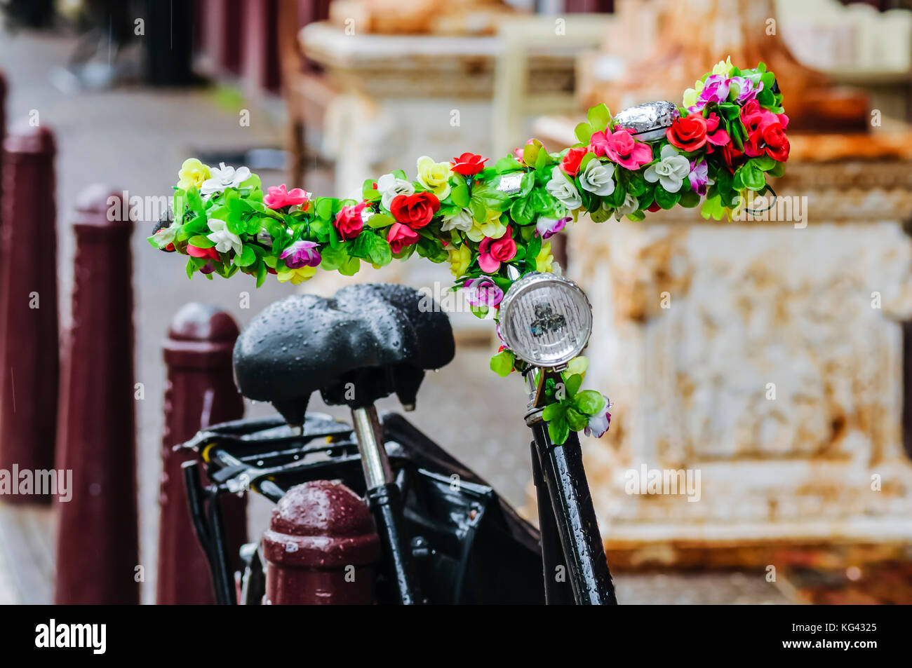 Dutch bicycle with its handlebars decorated with artificial flowers - Stock Image