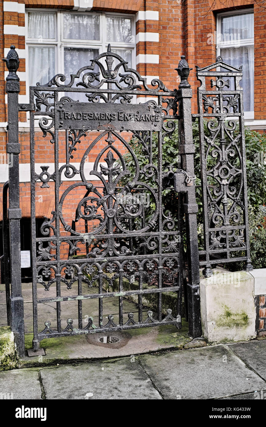 Wrought iron gate with sign saying Tradesmens Entrance to a block of expensive and exlcusive flats in Mayfair in - Stock Image