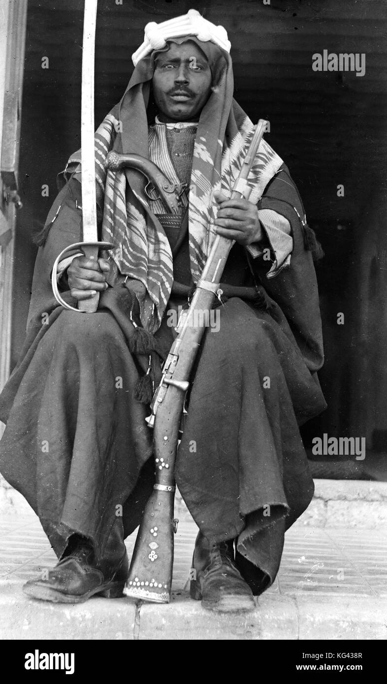 Archive black and white image of a Bedouin soldier armed with a rifle, sword and pistol circa 1920's - Stock Image