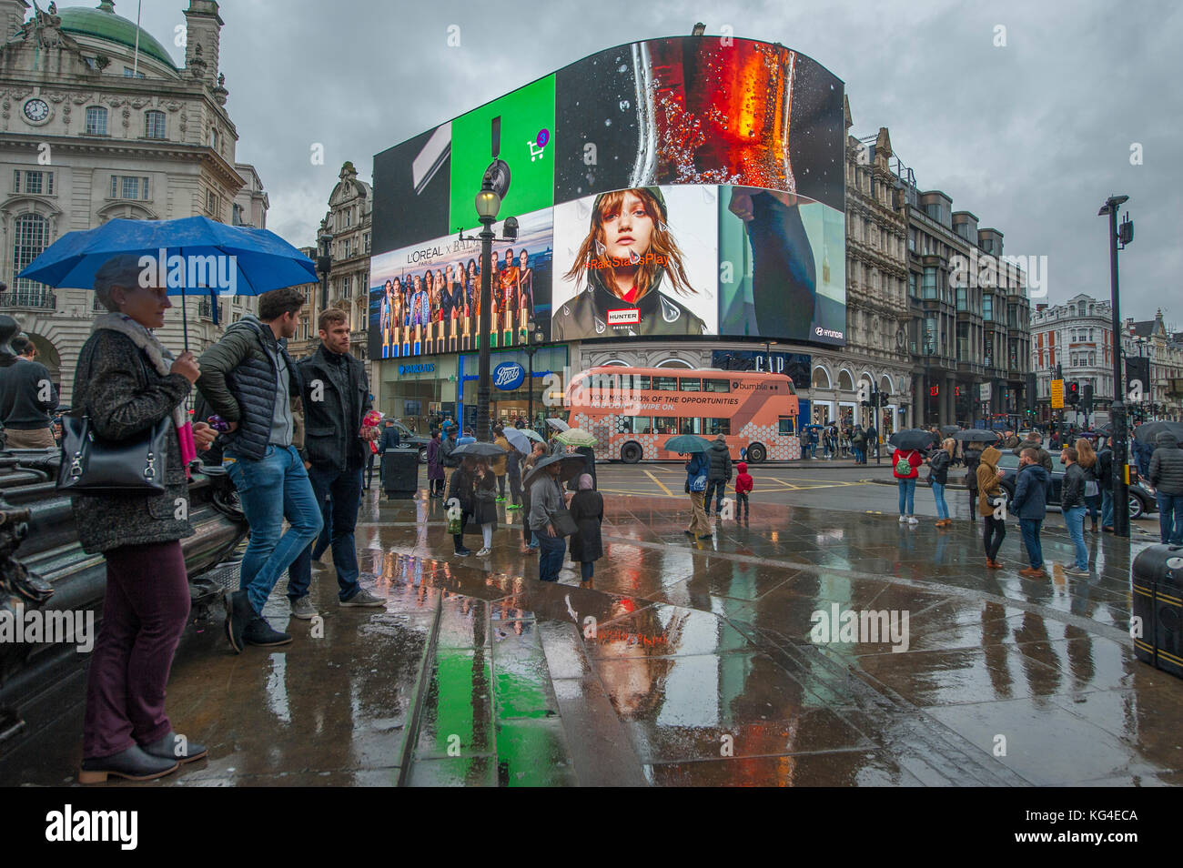 Piccadilly, London, UK. 4 November, 2017. New advertising signs the only bright splash of colour on a cold and wet Stock Photo