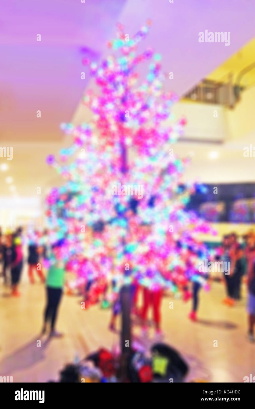 Blurred background of a Christmas tree with beautiful lights in a shopping center - Stock Image