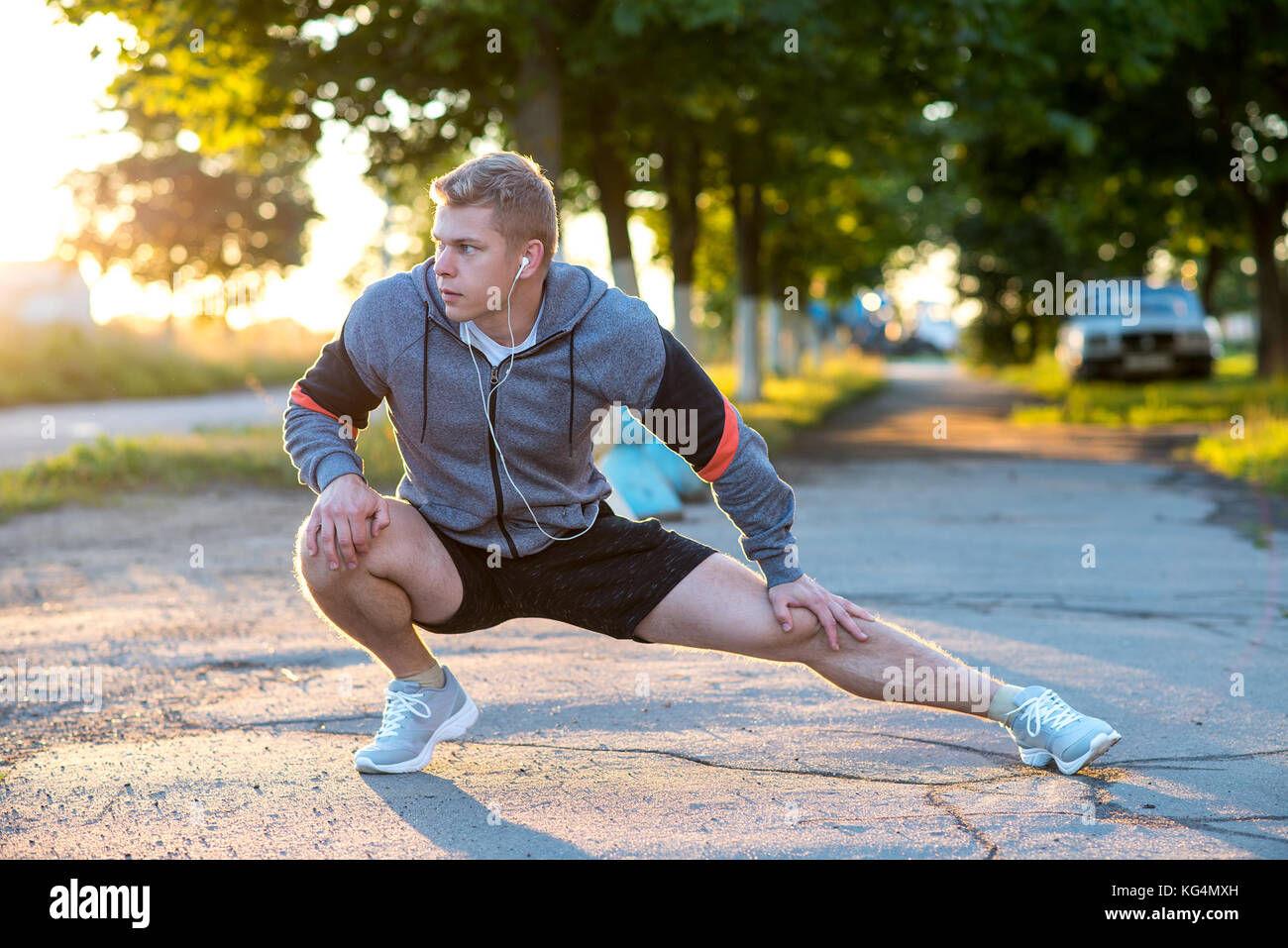 A young guy runner early morning makes gymnastics feet headphones. A warm-up joints muscles, man park listening - Stock Image