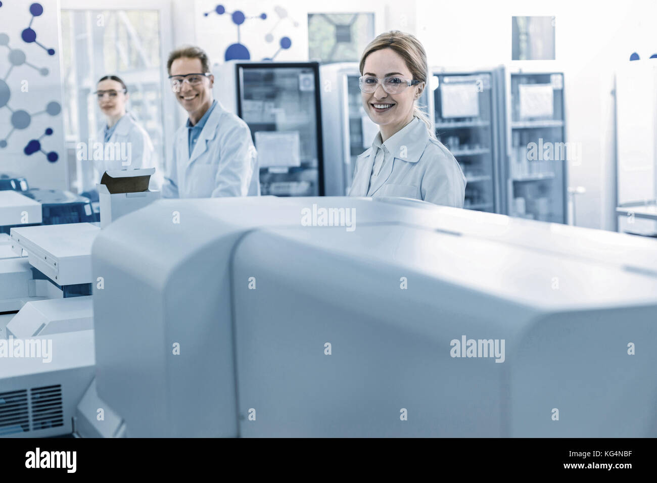 Delighted professional scientists smiling - Stock Image