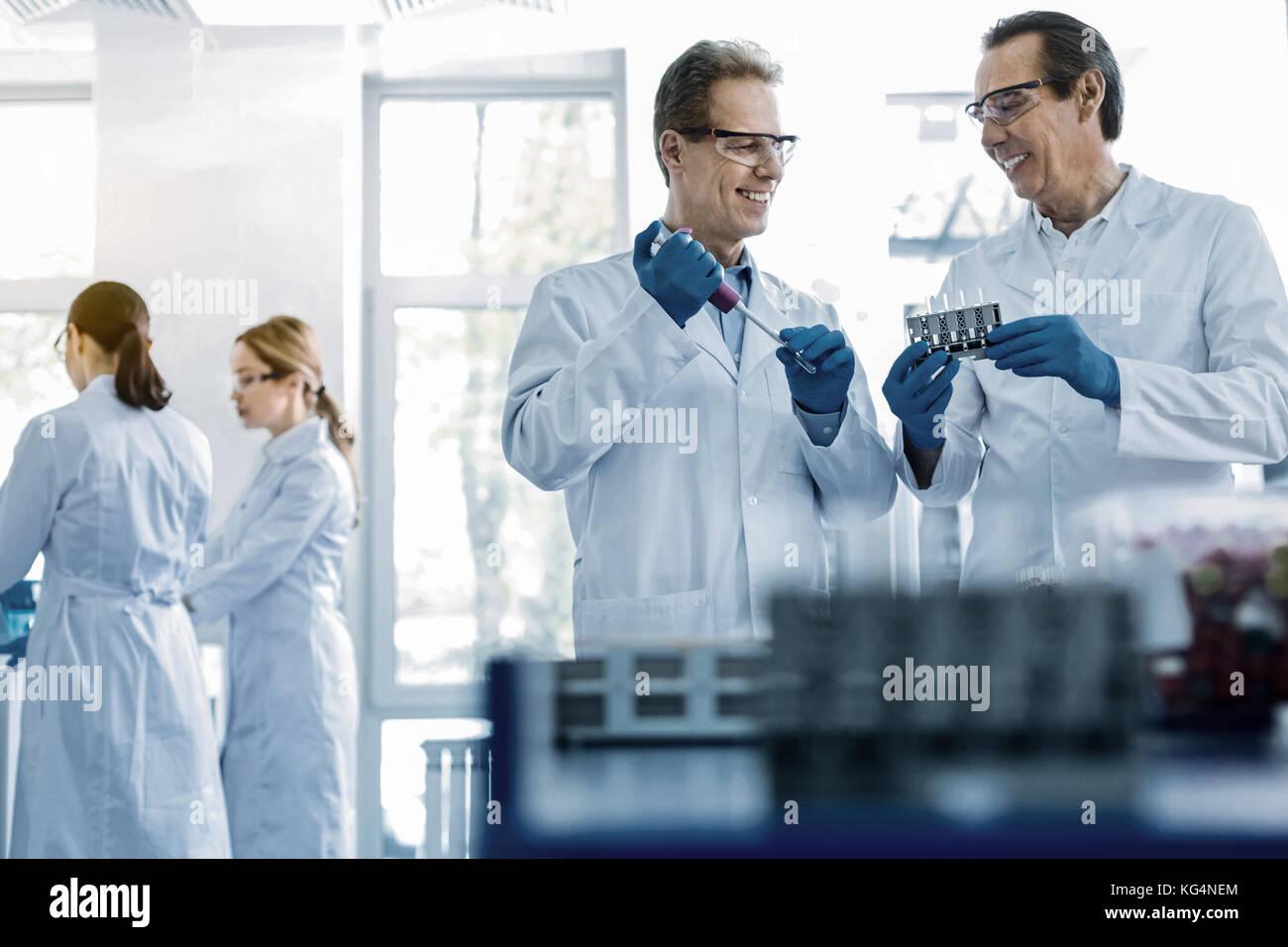 Joyful smart scientists working in team - Stock Image
