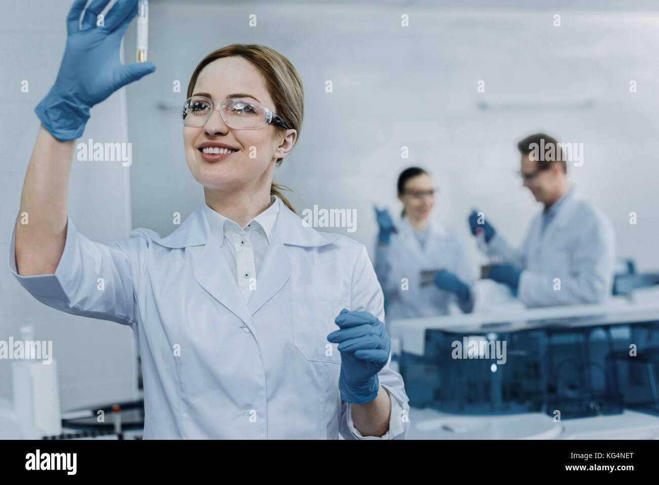 Cheerful successful scientist looking at the test tube - Stock Image