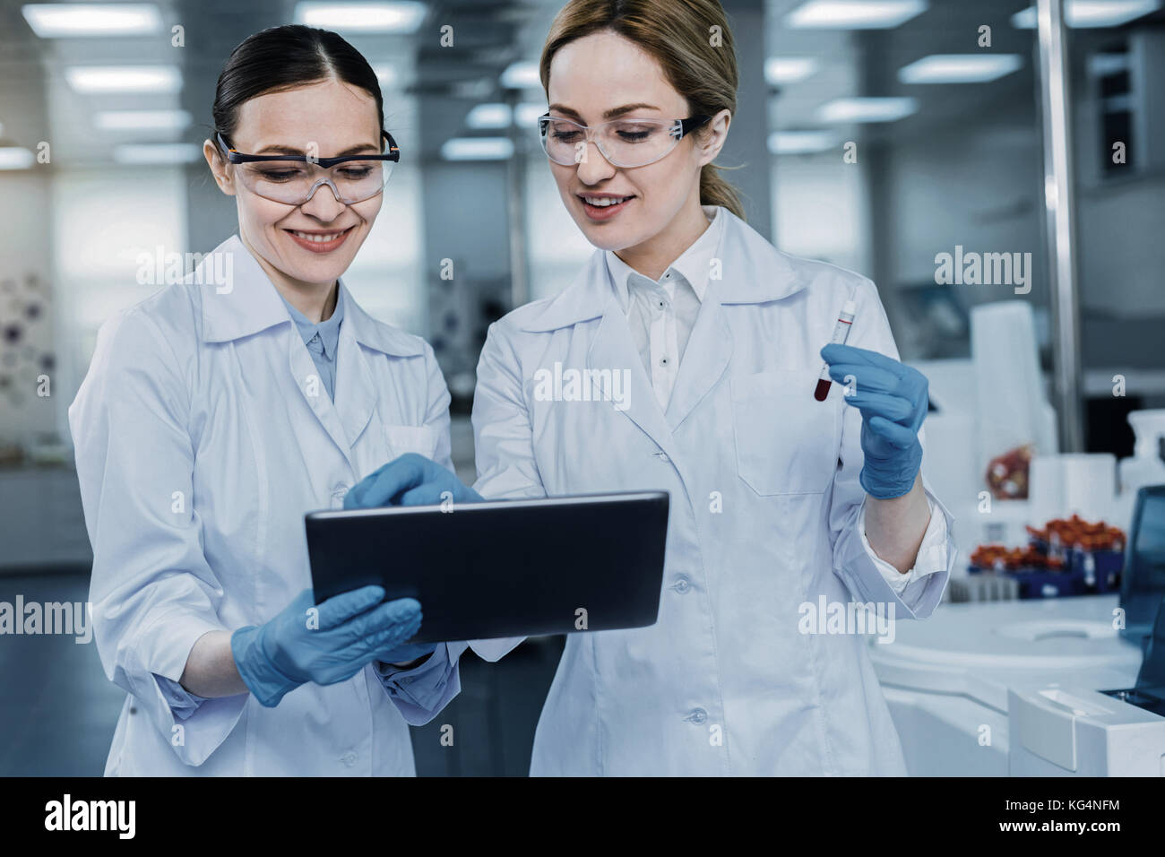 Joyful positive woman working together with colleague - Stock Image