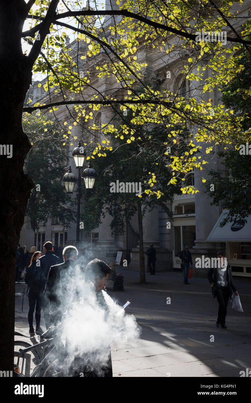 A vaper standing in Autumn sunshine exhales smoke from his eCigarette, on 27th October 2017, in the City of London, - Stock Image