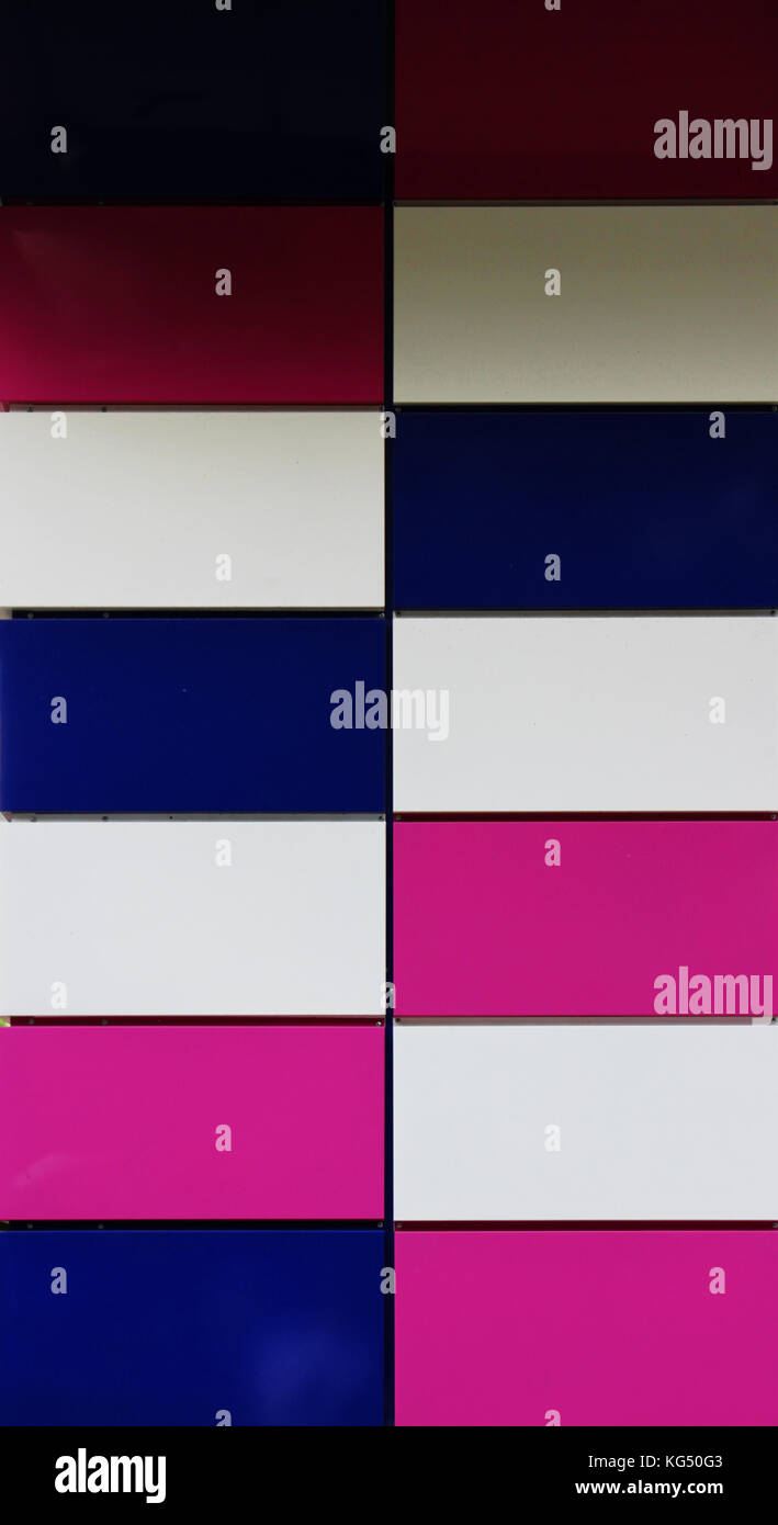 colorful white, crimson and purple rectangular panels on the wall of the house. - Stock Image