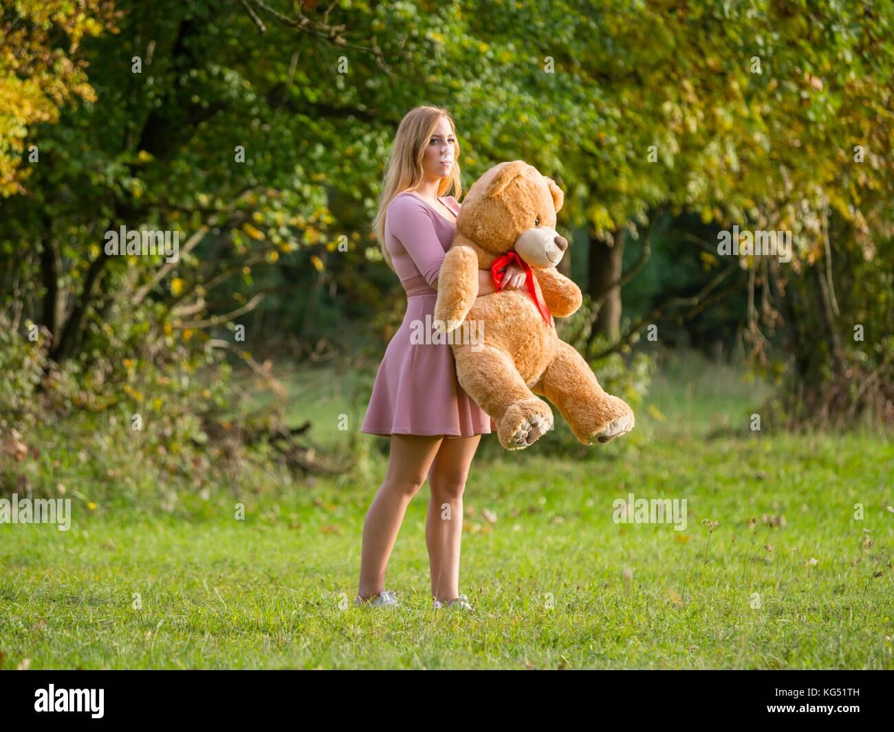 Teen girl with teddy-bear on green-field - Stock Image