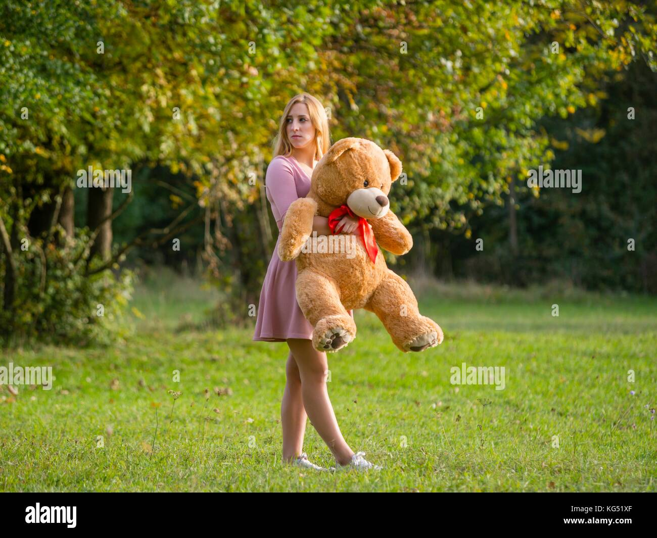 Stalked teen girl with teddy-bear on green-field - Stock Image
