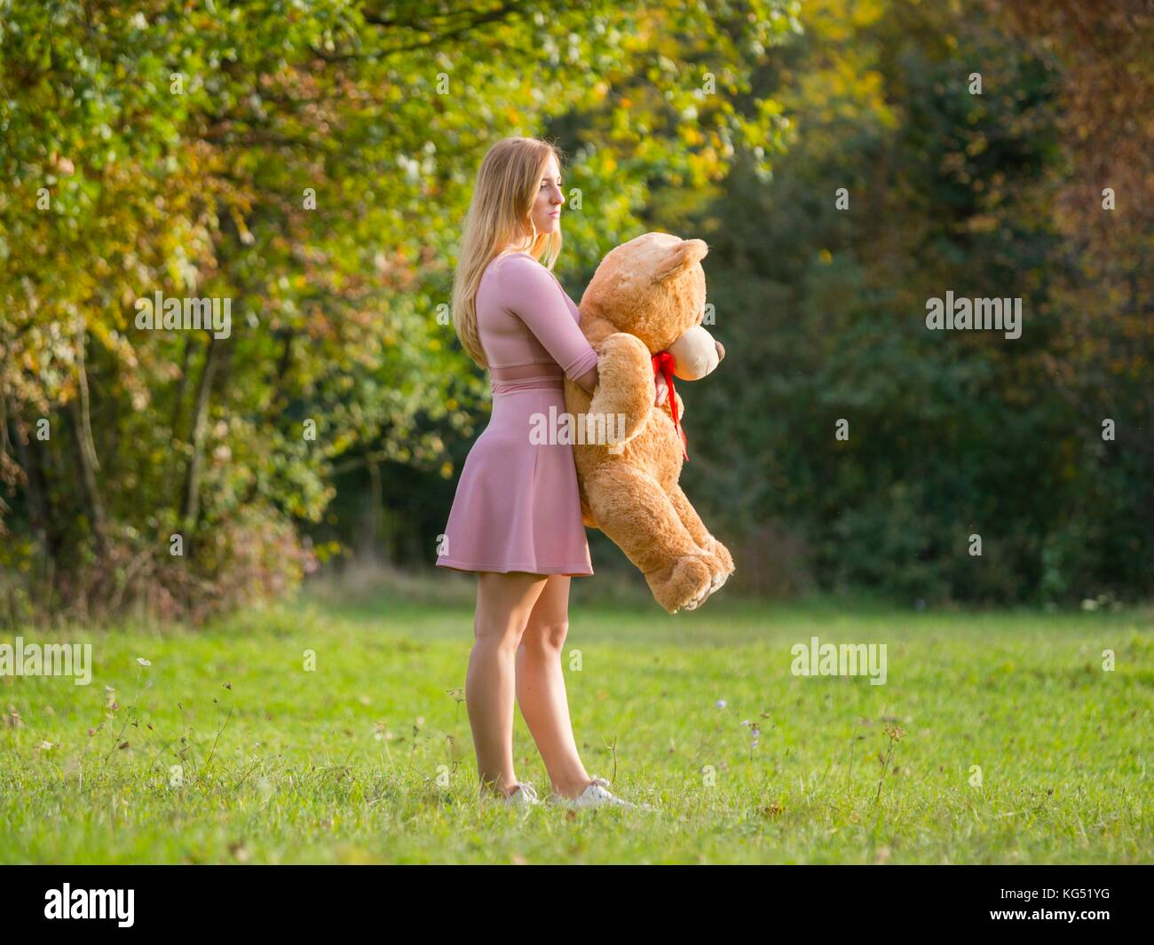 Teen girl with teddy-bear on green-field apparently almost evidently - Stock Image