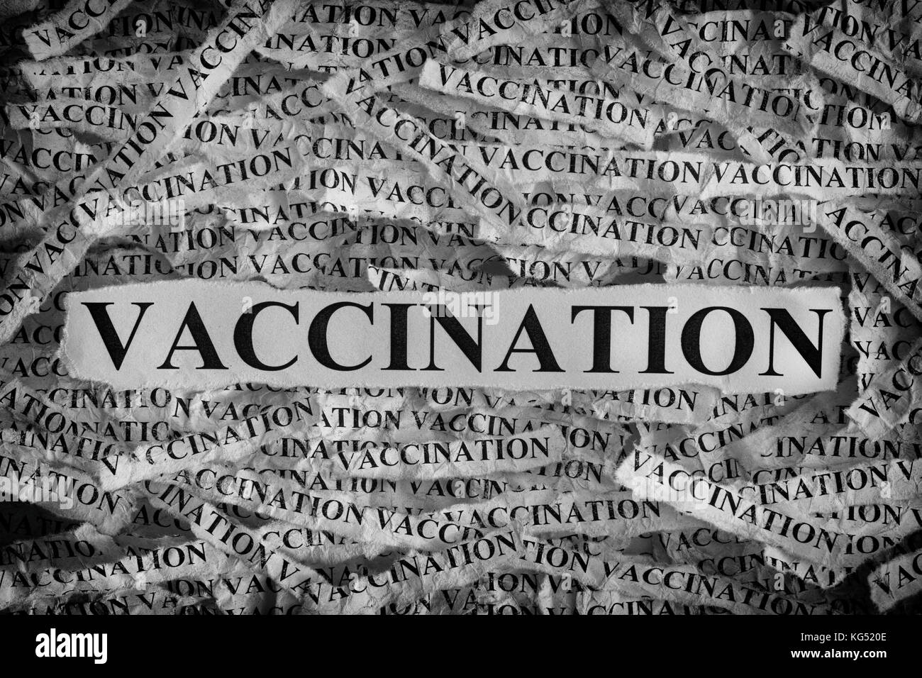 Vaccination. Torn pieces of paper with word Vaccination. Concept Image. Black and White. Closeup. - Stock Image