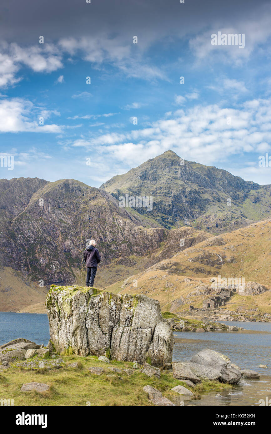 Solitary man stands on a rock and gazes at the peak of mount Snowdon, the highest mountain in England and Wales. - Stock Image