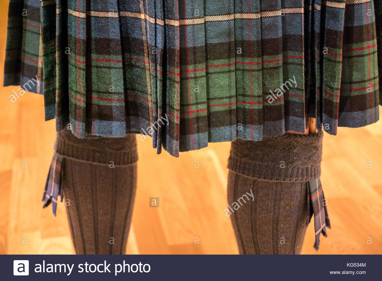 Close up of the back of a man wearing a MacRae tartan kilt, with kilt socks, flashes and Sgian dubh - Stock Image