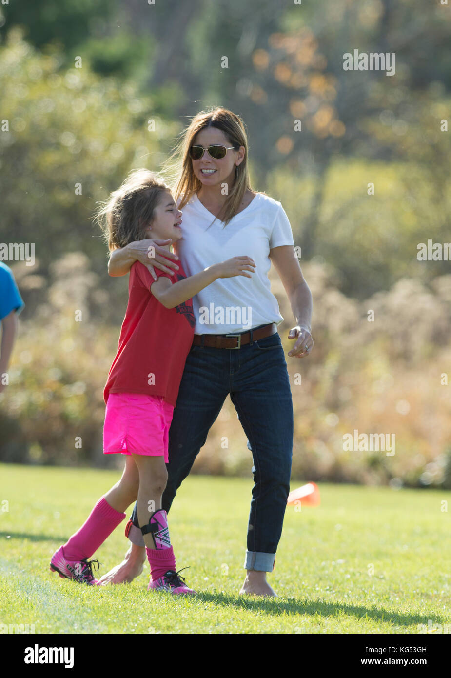 A 6yr. old girl is consoled by her mother after hurts while playing in a soccer match.  Waterbury, Vermont, USA - Stock Image