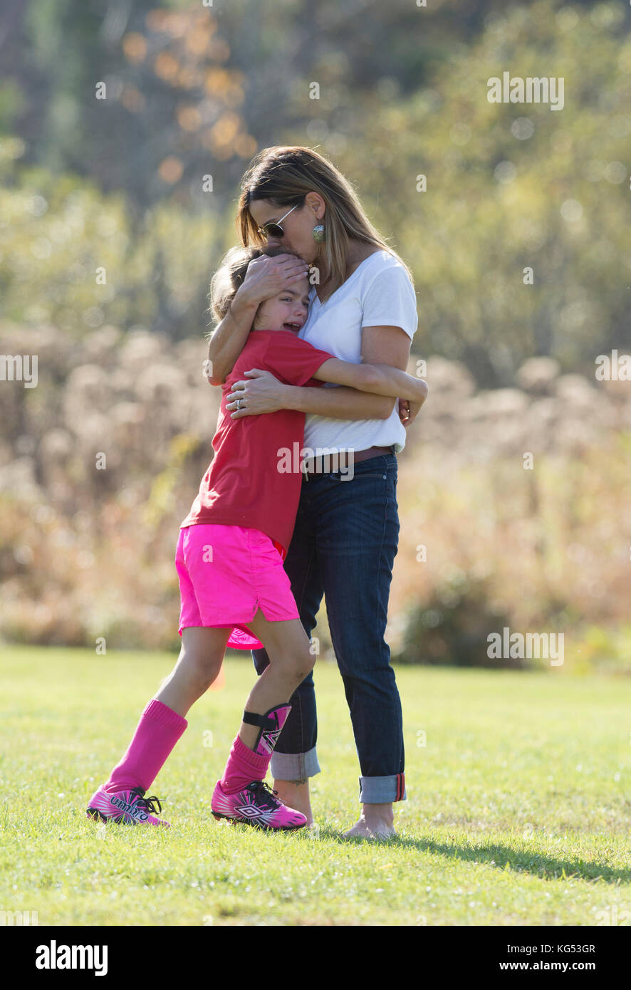 A 6yr. old girl playing in a soccer match is consoled by her mother following being hurt.  Waterbury, Vermont, USA - Stock Image