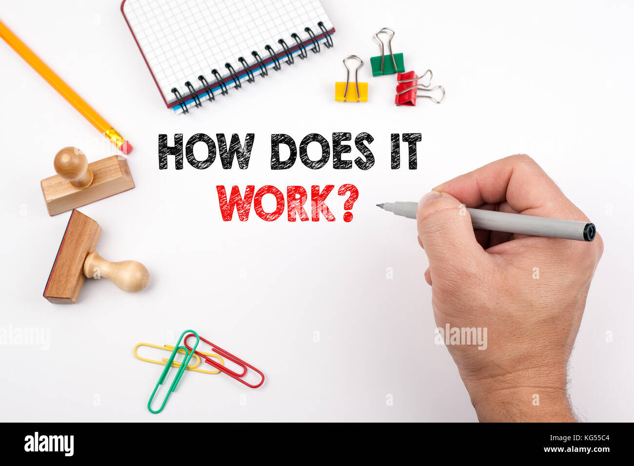 How Does It Work. White office desk on which various items - Stock Image