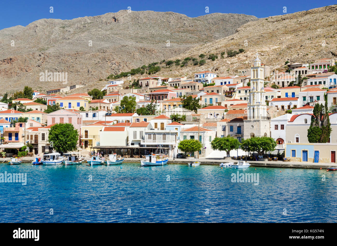 Taverna and boat lined waterfront of the port town of Emborios, Halki Island, Dodecanese, Greece - Stock Image