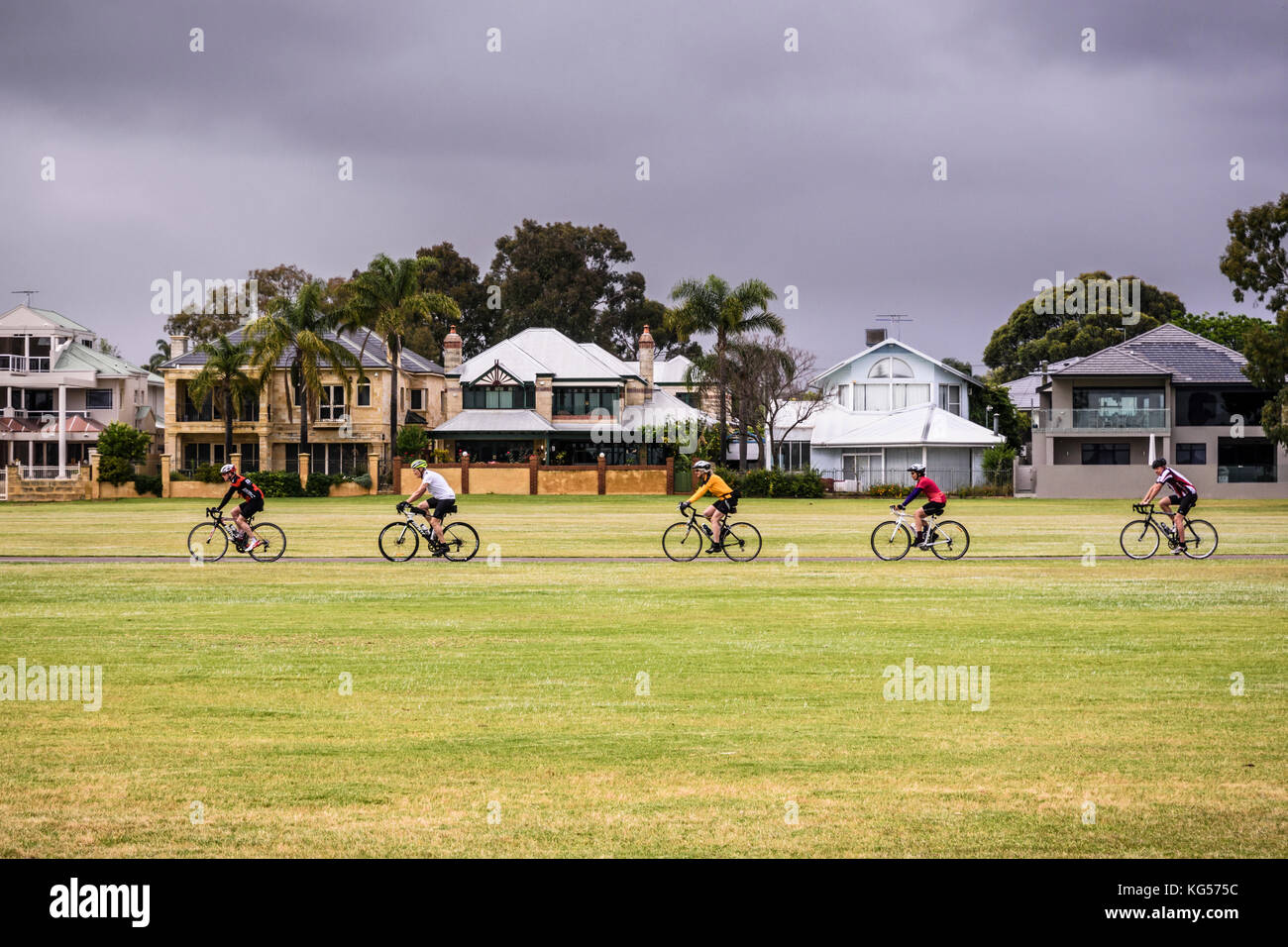 Cyclists braving bad weather along the cyclepath on the South Perth foreshore, Western Australia - Stock Image